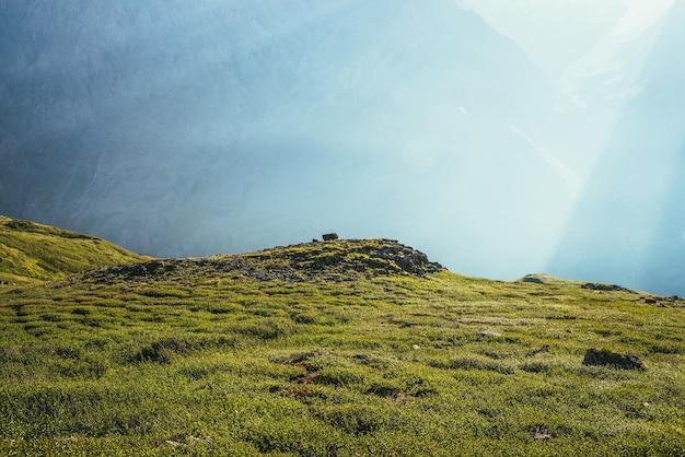 日光の下で巨大な山の壁の背景に岩や丘とカラフルな緑の風景。太陽光線と太陽フレアのあるミニマリストの鮮やかな日当たりの良い風景。最小限の高山ビュー。風光明媚なミニマリズム。