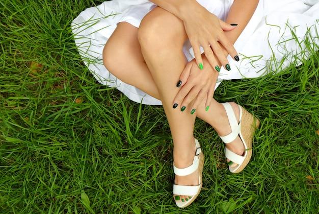 カラフルな緑のマニキュアと草の背景に白いウェッジヒールとペディキュア