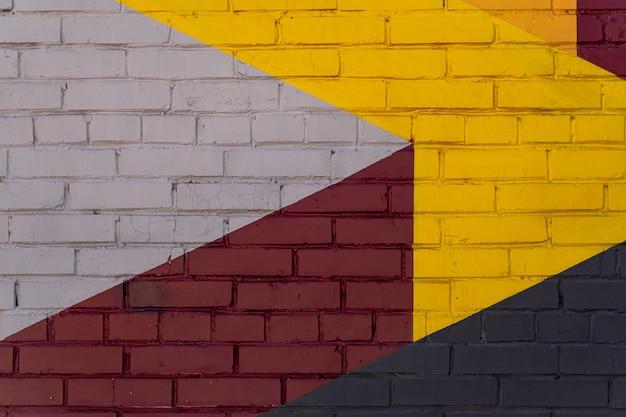 배경, 질감으로 다채로운 회색, 빨간색, 노란색 벽돌 벽.
