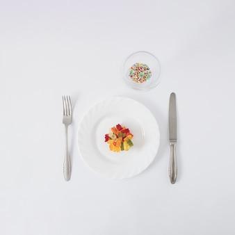 Разноцветные мармеладные мишки подаются на тарелке и стакане, полном разноцветных конфет. минимальная творческая концепция на белом фоне.