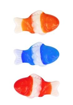 白い背景の上の緑、赤、オレンジ、黄色のカラフルなグミキャンディー魚