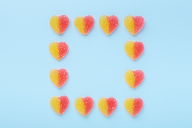 Красочные липкие сердца на синем столе. желейные конфеты.