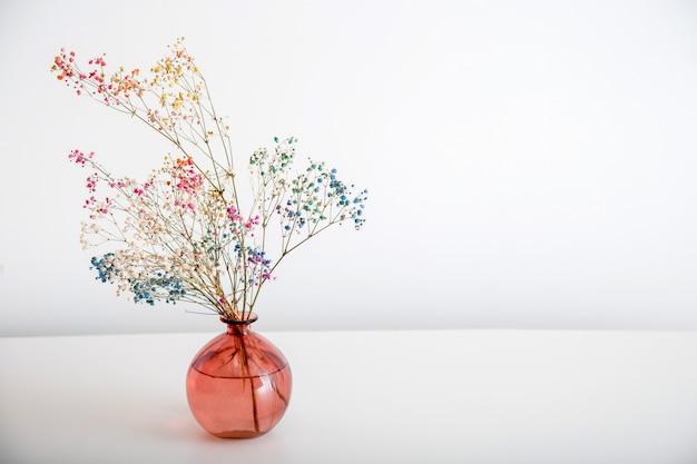 복사 공간이 있는 흰색 배경에 분홍색 꽃병에 다채로운 석고꽃. 흰 벽 앞에 꽃이 핀 말린 꽃다발.