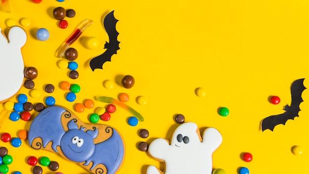 カラフルなハロウィンのキャンディーと紙のコウモリ