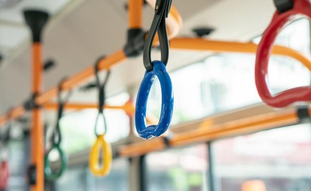 大学の公共の電気バス、車の輸送の内部で立っている乗客のためのカラフルなハンドル