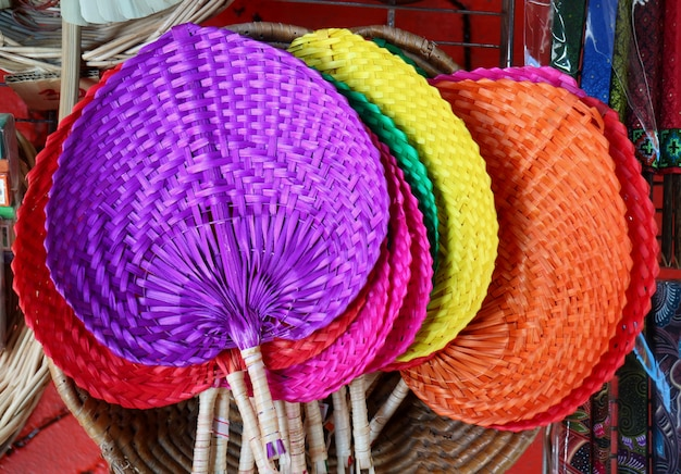 Colorful handmade natural raffia fans displayed in the shop at flea market in thailand