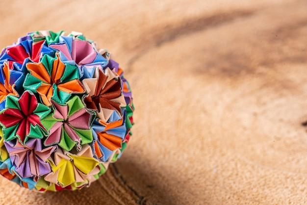 木製の背景にカラフルな手作り折り紙キーホルダー