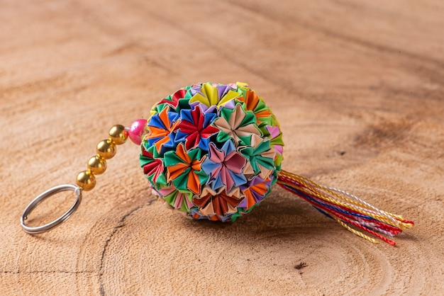 Colorful handmade origami keychain on a wooden background