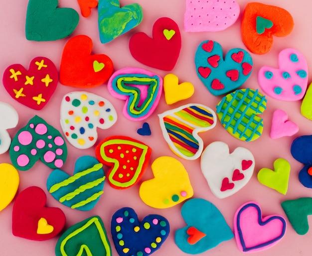 Colorful handmade plasticine hearts on pink