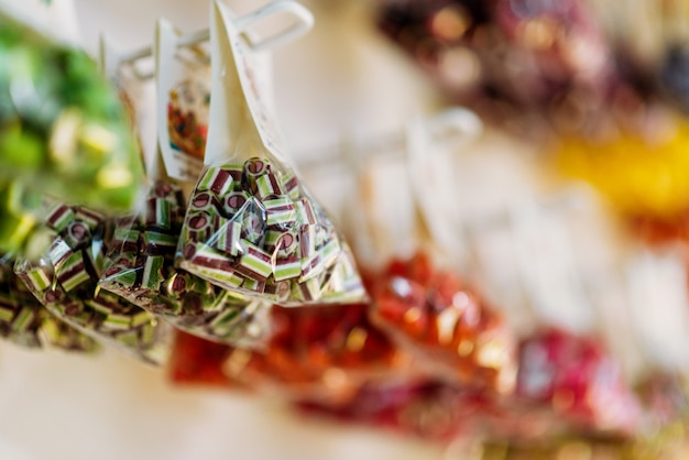 Красочные конфеты ручной работы сахарной карамели, упакованные в прозрачные пакеты крупным планом, никто. продукты в кондитерской. лакомства для детей