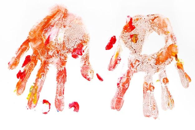 白い背景で隔離の子供たちによって手描きのカラフルな手形