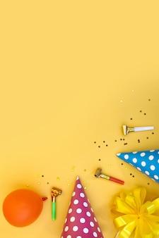 다채로운 생일 또는 파티 배경 플랫 레이에는 생일 모자, 송풍기, 색종이 조각, 리본이 노란색 배경에 있습니다. 복사 공간이 있는 상위 뷰입니다.