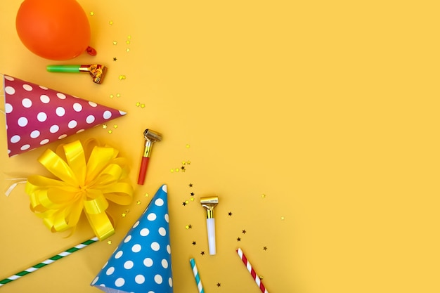 Colorful happy birthday or party background flat lay with birthday hats, blowers, confetti and ribbons on yellow background. top view with copy space.