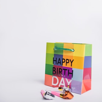Colorful happy birthday shopping bag with party blowers on white background