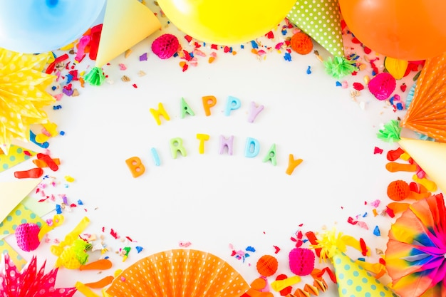 Colorful happy birthday text surrounded with party accessories on white backdrop