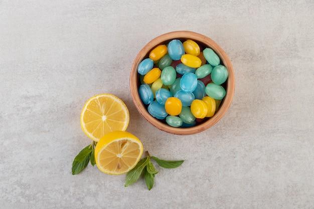 石のテーブルに置かれたスライスされたレモンとボウルのカラフルなハードキャンディー。