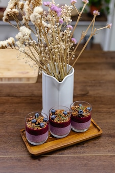 Colorful healthy breakfast sweet deserts few different chia puddings in glass jars on wooden table in kitchen at home.