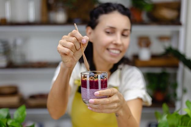 Colorata colazione sana dolce deserti alcuni budini di chia diversi in barattoli di vetro sul tavolo di legno in cucina a casa.