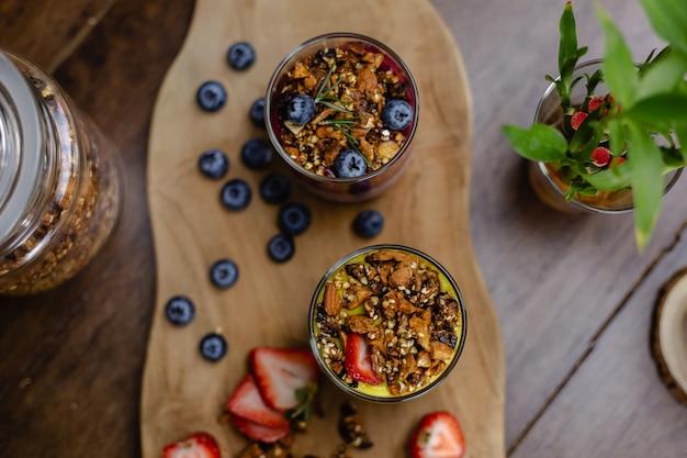 カラフルでヘルシーな朝食の甘いデザートは、自宅のキッチンの木製テーブルにあるガラスの瓶にいくつかの異なるチアプディングを入れています。
