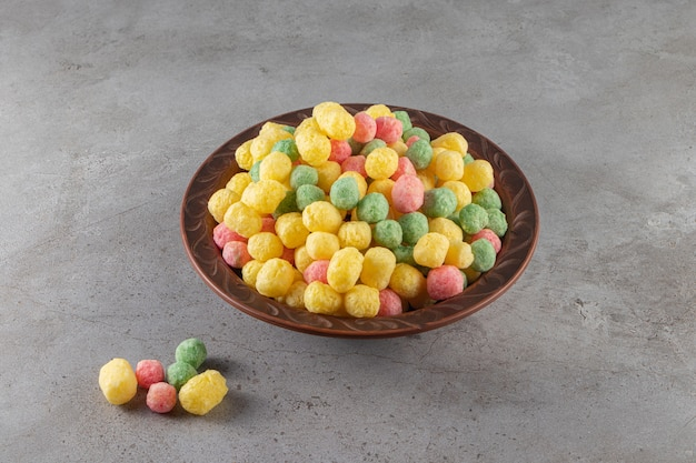 Colorful healthy cereal balls placed in a ceramic bowl.