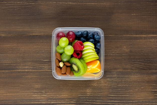 Colorful healthy mixed fruits with almonds in takeaway box