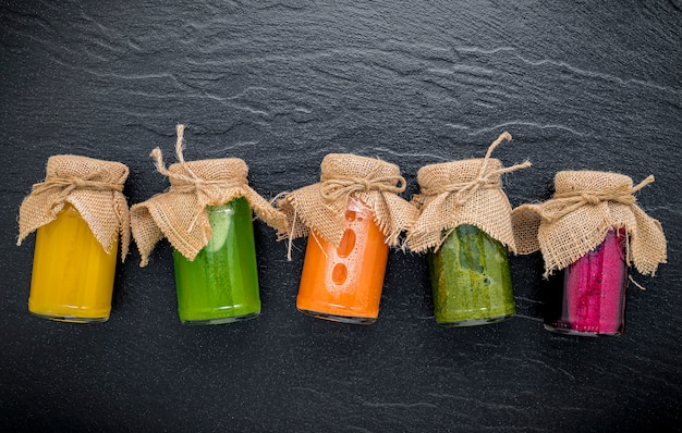 Colorful healthy smoothies and juices in bottles on dark stone