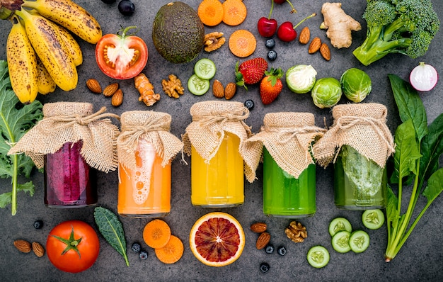Colorful healthy smoothies and juices in bottles with fresh tropical fruit and superfoods on dark stone