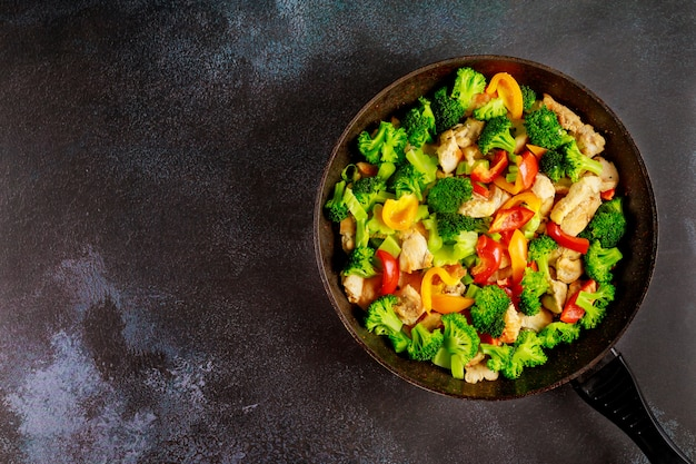 Colorful and healthy stir fry vegetables with chicken on dark surface