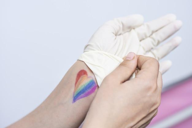Bandiera dell'orgoglio colorata a forma di cuore sulla mano di una persona