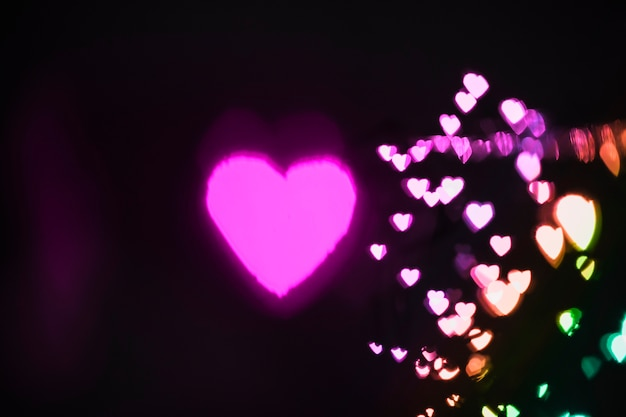 Colorful hearts near pink one