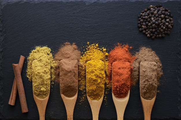 Colorful herbs and spices in wooden spoons on black stone table,  top view.