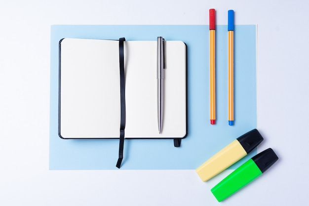 Colorful highlighters, pen, markers, notebook and blank paper to work or study