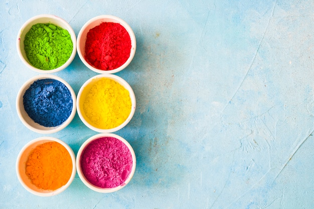 Colorful holi color powder inside the white bowls on painted blue backdrop