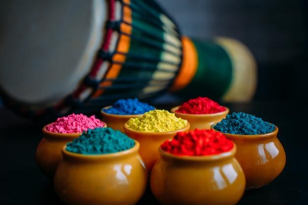 컵 근접 촬영에서 화려한 holi 분말입니다. 점토 냄비에 인도 holi 축제를위한 밝은 색상. 선택적 초점. 인도 드럼 djembe의 배경. 검은 색과 파란색 배경, 선택적 초점