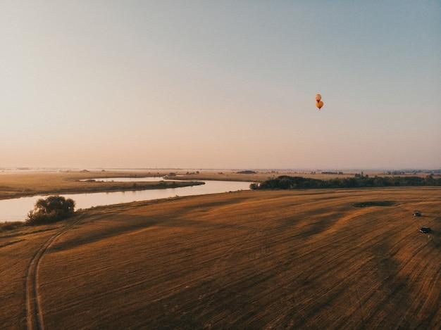 美しい空の背景と日の出の霧の上を飛んでいるカラフルな熱気球の叙事詩
