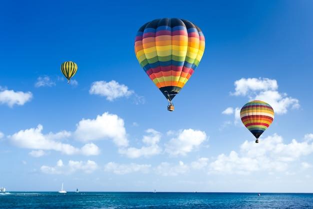 カラフルな熱気球が青い海の上を飛ぶ