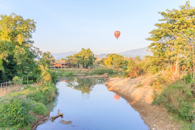 Colorful hot air balloon over mountain and song river vangvieng, laos