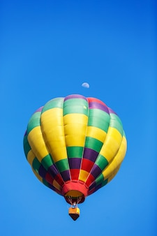 Colorful hot air balloon with moon in blue sky