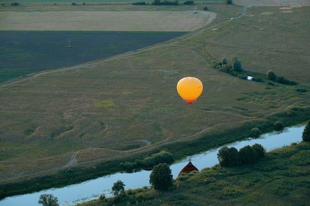 カラフルな熱気球が飛んでいます。バルーンフェスティバル。空と夕日、自然の静けさを背景にした気球。夏はいい天気