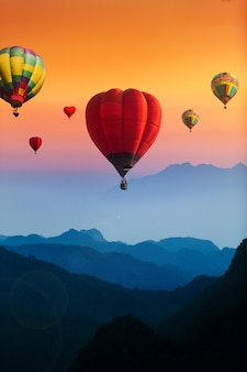 Colorful hot air balloons flying over blue mountains