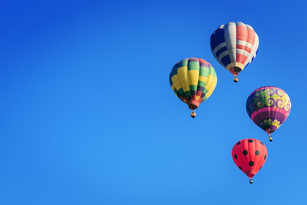 Colorful hot-air balloons flying in blue sky