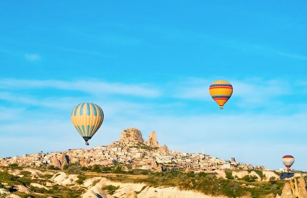 日の出、カッパドキア、トルコのウチヒサール城の近くを飛んでいるカラフルな熱気球