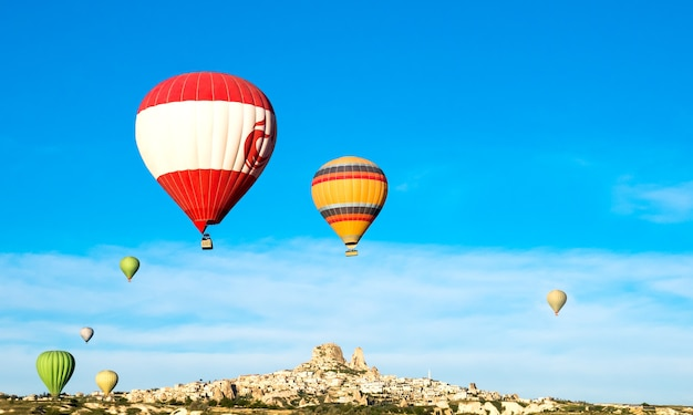 Красочные воздушные шары летают возле замка учхисар на рассвете, каппадокия, турция