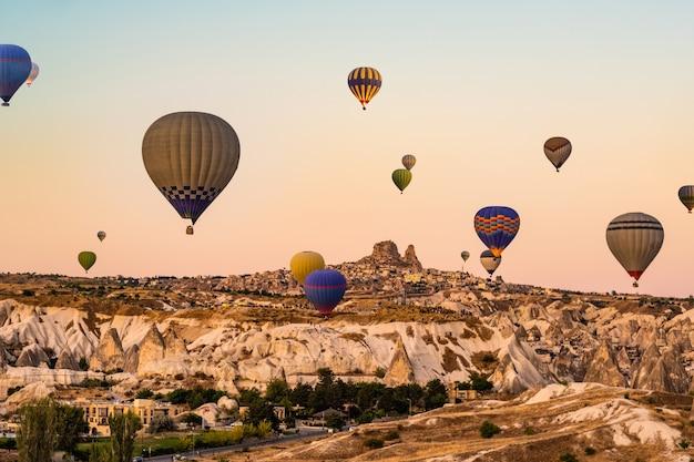美しい夕焼け空にカッパドキア七面鳥の美しい谷の上を飛んでいるカラフルな熱気球
