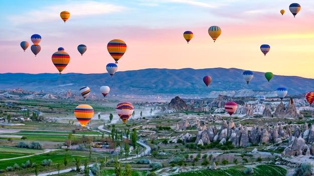 Красочные воздушные шары пролетели над скалистым ландшафтом в каппадокии, турция