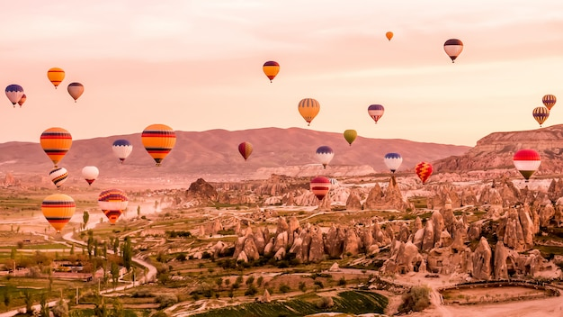 Colorful hot air balloons flying over rock landscape at cappadocia turkey