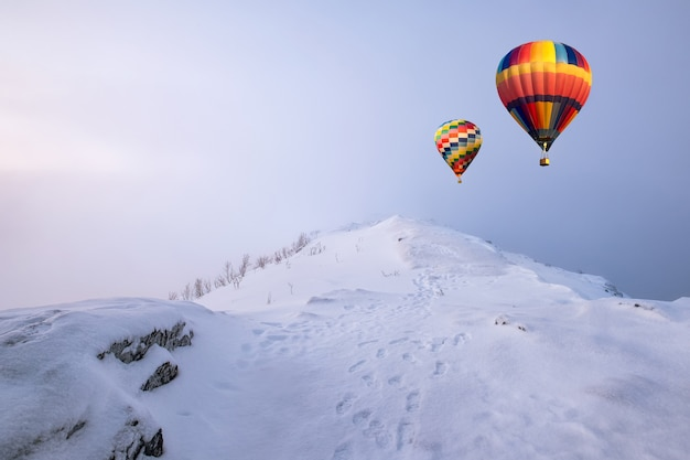 Colorful hot air balloons flying on snow hill with blizzard