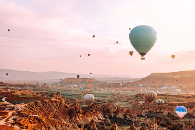 Colorful hot air balloons flying over the valley at cappadocia sunrise