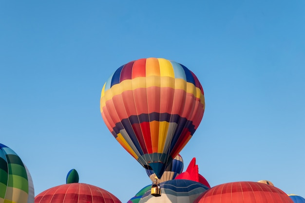 Colorful hot air balloons flying with blue sky in festival