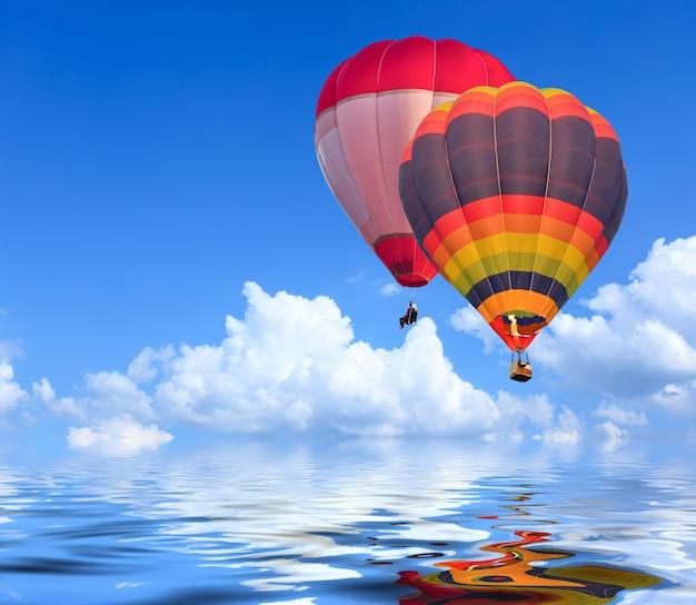 水の反射と青い空の上空を飛行中のカラフルな熱気球